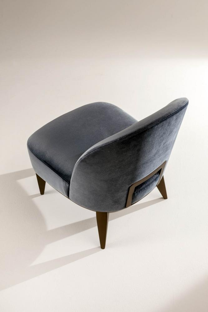 Margaret is a modern armchair in leather, velvet or fabric with wooden handle