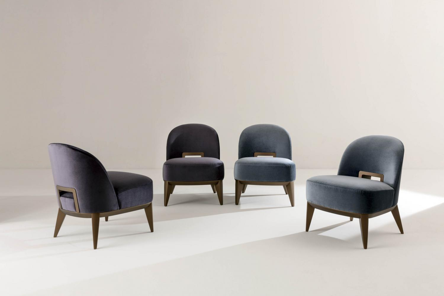 Margaret is a Modern armchair in leather velvet or fabric with wooden handle